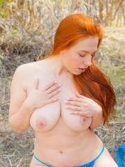 Busty redhead babe Titania shows her huge natural tits outside