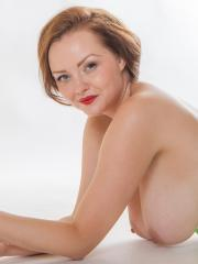 Busty redhead Natasha Dedov strips out of her green lingerie