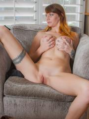 Redhead hottie Melissa Dangerous strips naked for you on the chair
