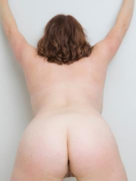 Maggie Green strips nude next to wall