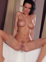 Stunning babe Lynette strips and plays with her wet pussy