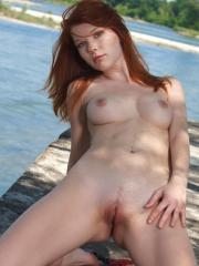 Stunning redhead Mia Sollis plays naked by the river
