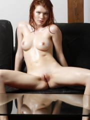Hot redhead Mia Sollis rubs oil all over her body