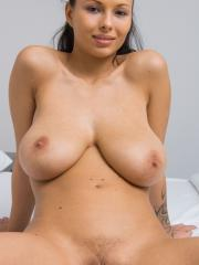 Busty brunette Domino gives you her nude body in bed