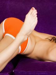 Pictures of Kayden Love teasing in her orange panties on the couch
